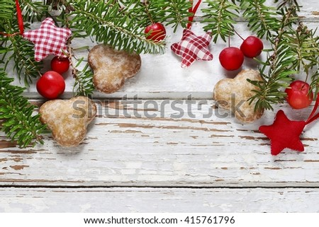 Christmas gingerbread cookies, fir branches and paradise apples on a white wooden background, copy space. - stock photo
