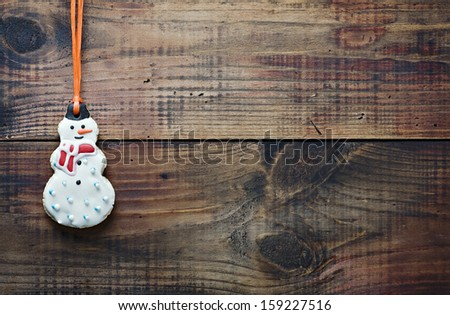 christmas gingerbread cookies hanging over wooden background - stock photo