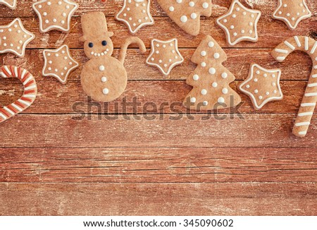 Christmas gingerbread cookies on a wooden table with space in the bottom part of the image.