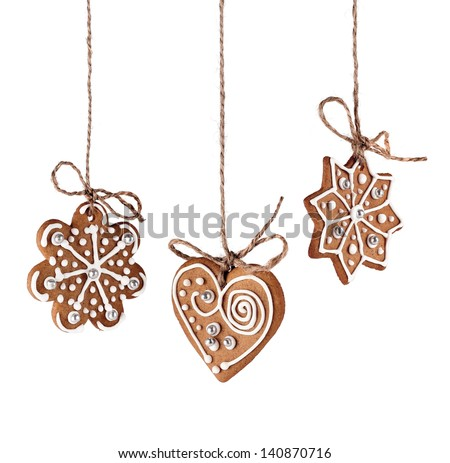 Christmas gingerbreads hanging in traditional linen string isolated - stock photo