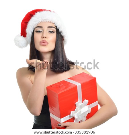 Christmas girl. Beautiful x-mas woman holding gift box and sending wind kiss over white background. - stock photo