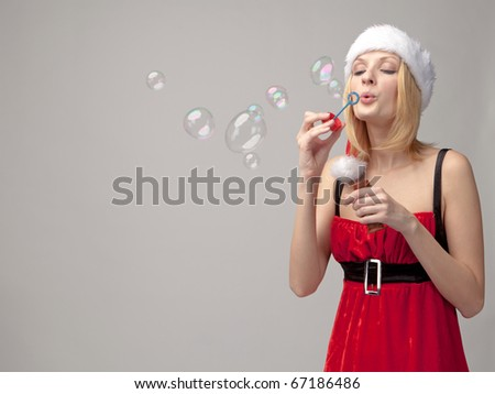Christmas girl in santa hat with bubble blower - stock photo
