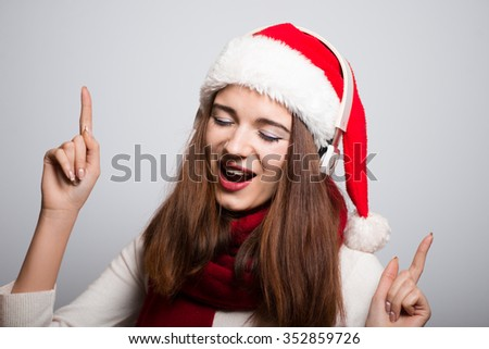 Christmas girl listening to music on headphones. Santa hat isolated portrait of a woman on a gray background. - stock photo