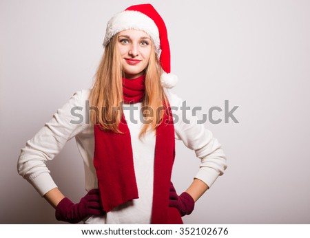 Christmas girl put her hands on her hips. Santa hat isolated portrait of a woman on a gray background. - stock photo