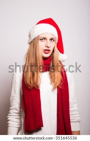 Christmas girl scared. Santa hat isolated portrait of a woman on a gray background. - stock photo