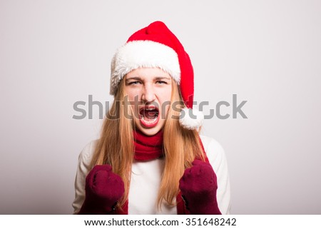 Christmas girl screaming Happy New Year. Santa hat isolated portrait of a woman on a gray background.