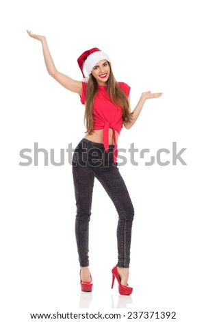 Christmas girl standing with arms outstretched and presenting product. Full length studio shot isolated on white. - stock photo