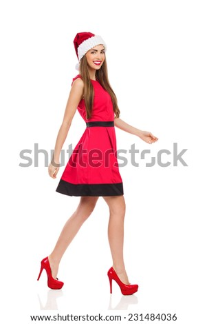 Christmas girl walking in red dress, santa's hat and high heels. Full length studio shot isolated on white. - stock photo