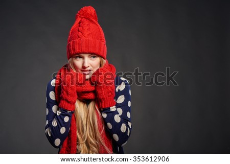 Christmas girl, winter concept. Young beautiful woman muffling in warm knitted scarf for warmth, over grey background - stock photo