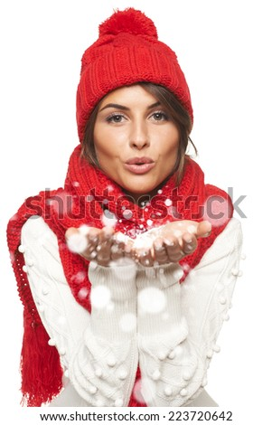 Christmas Girl. Woman wearing knitted warm red scarf and hat blowing snow at you, looking at camera, over white background - stock photo