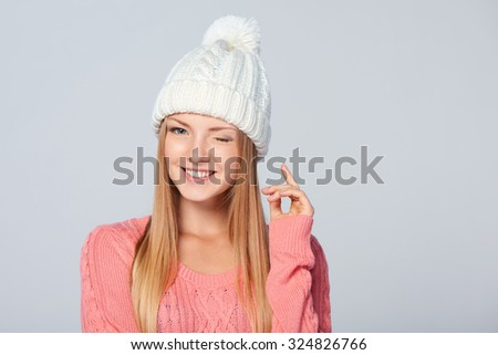 Christmas girl, young beautiful smiling woman giving a wink over grey background
