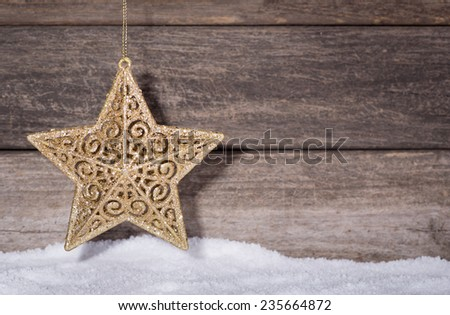 Christmas gold star hanging over snow with wooden background - stock photo
