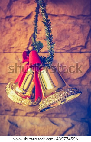 Christmas golden bells with a red bow hanging on the brick wall background. Vintage tone. - stock photo