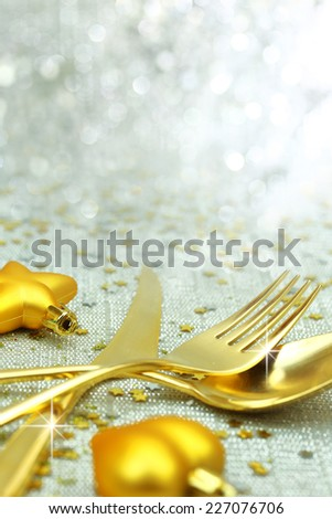 Christmas golden cutlery and ornaments on festive background - stock photo
