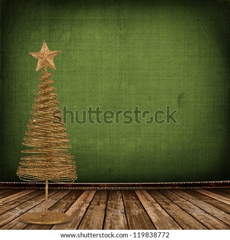 Christmas golden spruce in the old room, decorated with wallpaper - stock photo