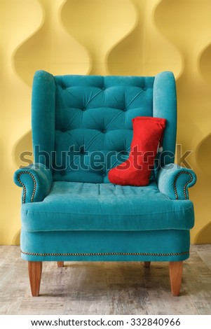 Christmas goods in red sock on blue armchair. Modern interior. Shallow DOF - stock photo