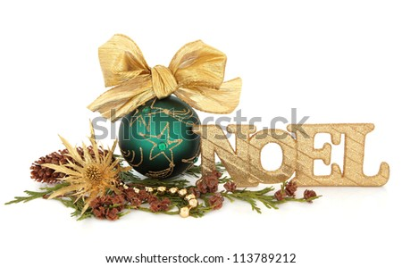 Christmas green bauble decoration with bow and gold noel sign surrounded by winter greenery over white background. - stock photo