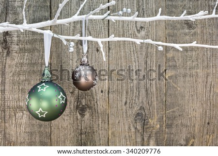 christmas green baubles hanging off a white bare branch on wooden rustic background - stock photo