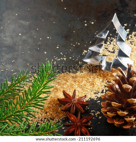Christmas greeting card background with a cookie cutter in the shape of a Christmas tree with a pine branch, cone, caramelized brown sugar and star anise spice on a dark background with copyspace - stock photo