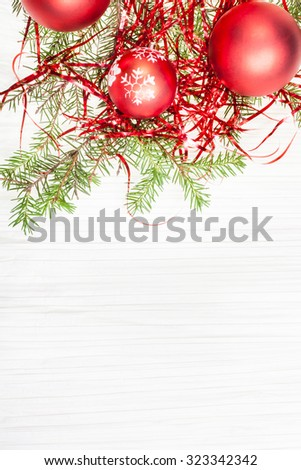 Christmas greeting card - border from red Xmas decorations and tree branch on blank paper background - stock photo