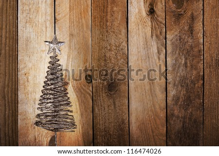 Christmas greeting card with gold metal firtree on the wooden background - stock photo