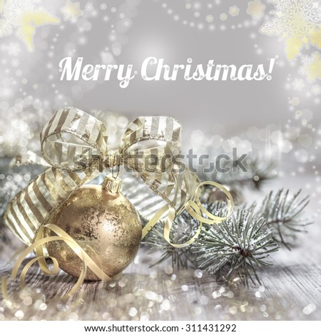 "Christmas greeting card with toys and decorations in green and gold, caption ""Merry Christmas!"". Shallow DOF, focus on the bauble crown and parts of the bow."