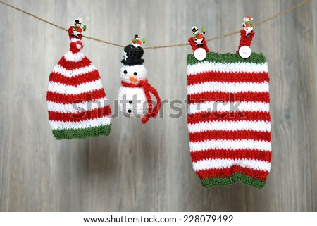 Christmas handmade baby pants, hat and snowman toy hanging on a clothesline - stock photo