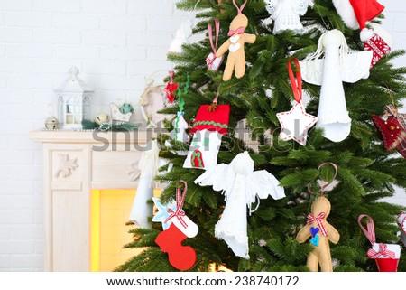 Christmas handmade decorations on Christmas tree  on light home interior background - stock photo