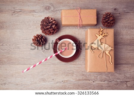 Christmas handmade gift boxes with cup of chocolate and pine corn on wooden table. View from above - stock photo