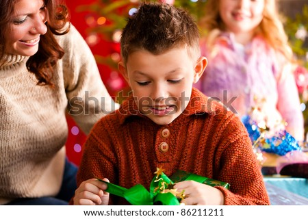 Christmas - happy family (mother with son and daughter) with gifts on Xmas Eve - stock photo