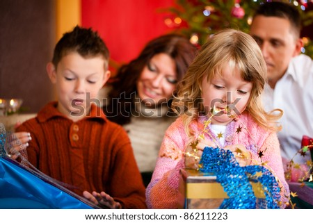 Christmas - happy family (parents with son and daughter) with gifts on Xmas Eve - stock photo