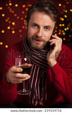 Christmas - happy smiling forty years old caucasian man with a glass of wine talking on mobile phone. Dark red with lights as background. - stock photo