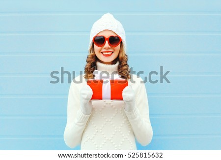 Christmas happy smiling young woman with gift box wearing a knitted hat sweater sunglasses over blue background
