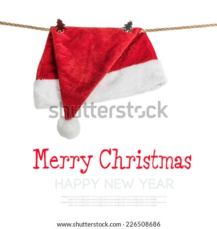Christmas Hat Santa claus hanging on a rope with clothespins on white background. - stock photo