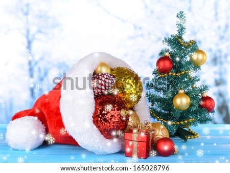 Christmas hat with Christmas decorations on table on light background  - stock photo