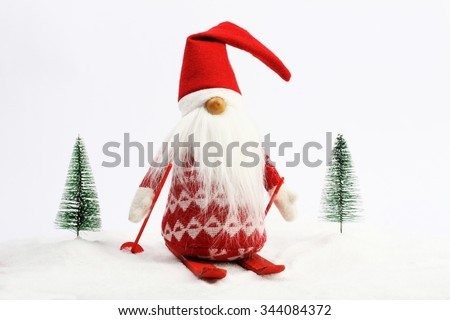 Christmas helper (elf) skiing on snow next two snowy trees Red and white colors - stock photo