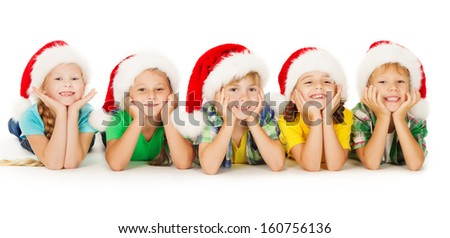 Christmas helpers children in Santa hat lying down. Smiling group of happy kids over white background.  - stock photo