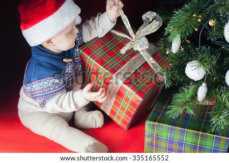 Christmas holiday. Baby in Santa hat opening a box of gifts. Sitting under the tree on a red background. Angry and nibbles tape. Can not open. New Year. Night - stock photo