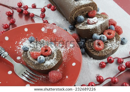 Christmas holiday chocolate roulade yule log swiss roll with berries dessert party food on red wood background. - stock photo
