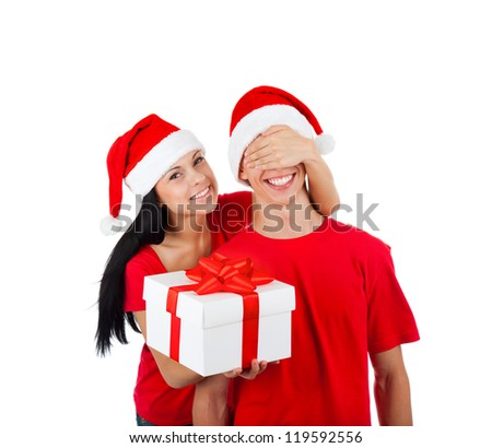 christmas holiday couple happy young woman surprise boyfriend cover his eyes, female covering mans eyes, excited smile, isolated over white background wear red new year hats and shirts - stock photo