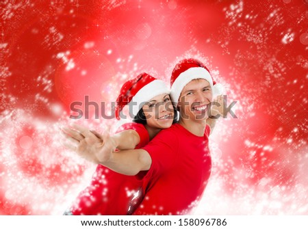 christmas holiday couple love smiling with hands outstretched lifted upwards, man and woman smile wear red shirts and new year hat, over abstract magic winter background with sparkles blowing snow - stock photo