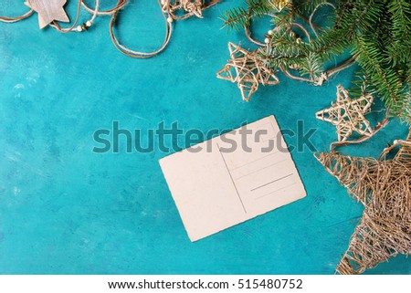 Christmas holiday decor with golden stars, thread, empty greeting card and fir tree over turquoise wood texture surface with copy space. Top view. Christmas background theme.