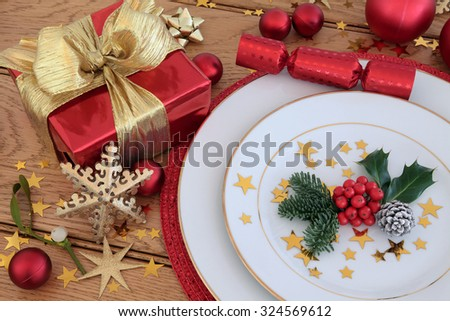 Christmas holiday dinner place setting with plates, gift box, bauble decorations, holly and mistletoe over oak table  background. - stock photo