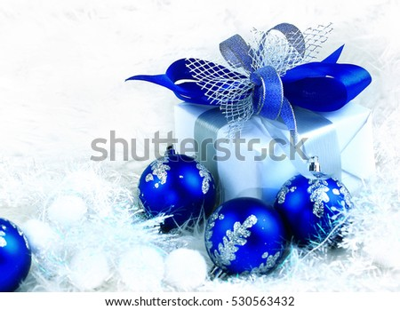 Christmas. holiday gift in a beautiful package and blue glass balls on festive background.in the photo there is an empty space for your text