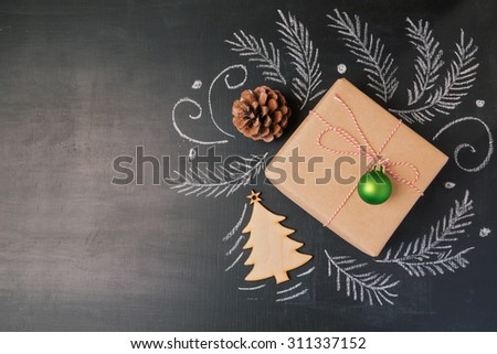 Christmas holiday gift on chalkboard background. View from above with copy space - stock photo