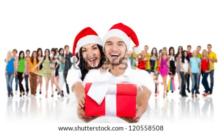 christmas holiday happy couple hold present gift box wear red new year santa hat cap, man and woman love smile over big group of casual people diverse student background