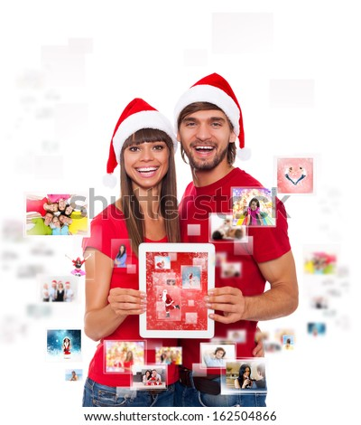christmas holiday happy couple hold tablet pad computer present wear santa hat smile embracing, show touch screen, concept of new year social communication