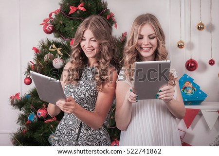 Christmas holiday happy girl friends using smartphones in christmas decorated living room. Shopping online or choosing gifts. Christmas, friendship and happiness concept.