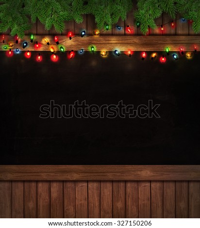 Christmas holiday lights on wooden blackboard - stock photo