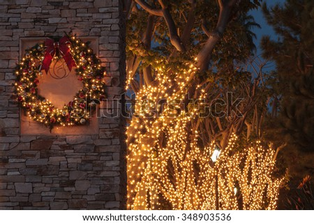 Christmas holiday wreath with white lights on a brick pillar - stock photo